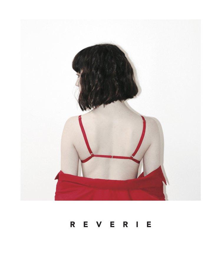 Długie i zdrowe włosy z Reverie. Kobieta, brunetka z fryzurą typu long bob pozuje w czerwonej stylizacji.u