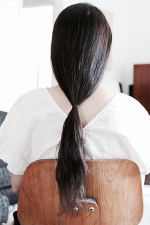 Długie i zdrowe włosy z Reverie. Kobieta z długimi ciemnymi włosami siedzi na krześle.